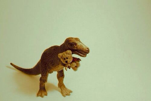 Dinosaur hugging a Teddy Bear