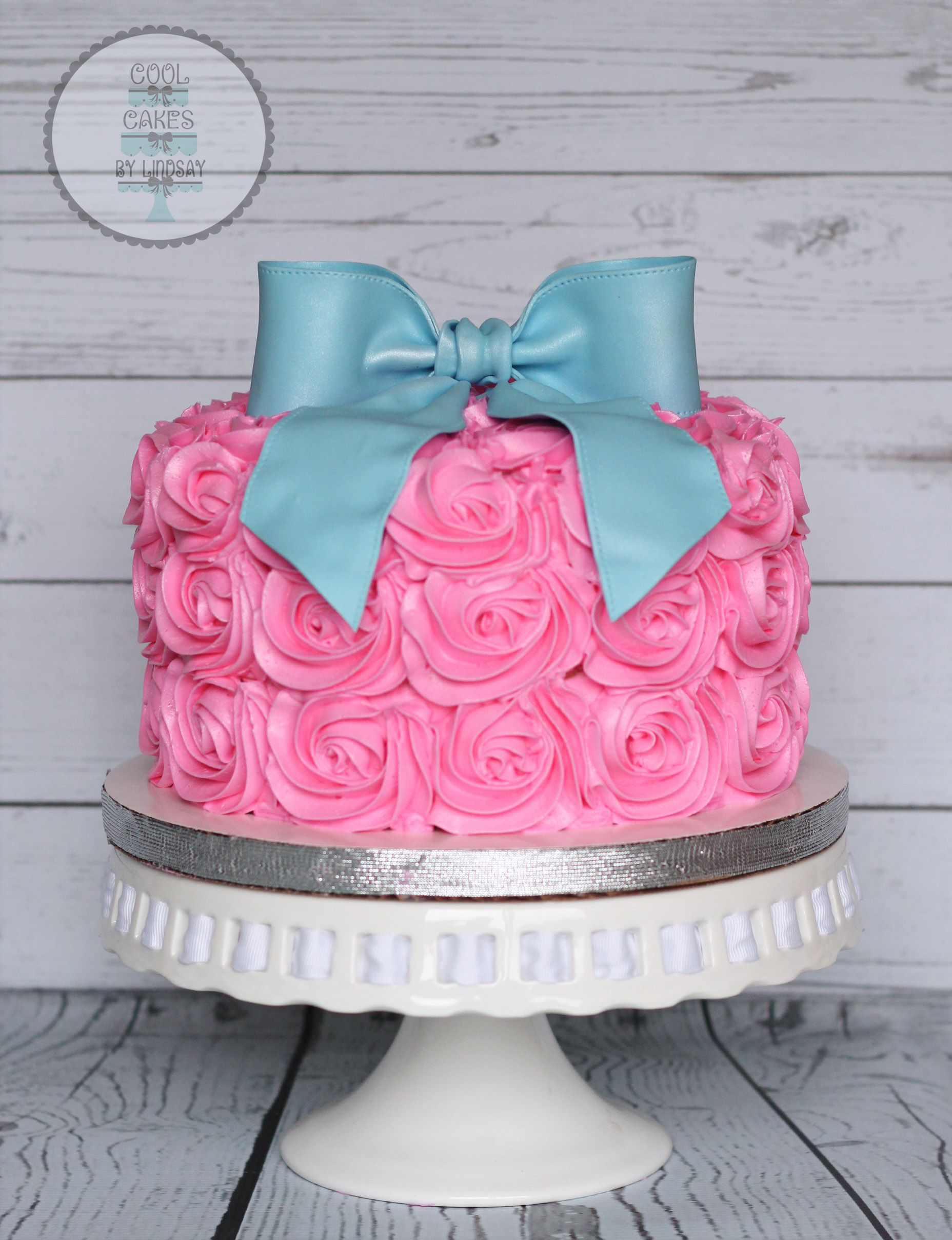 Pink and blue Gender reveal cake Pink rosettes and blue fondant bow
