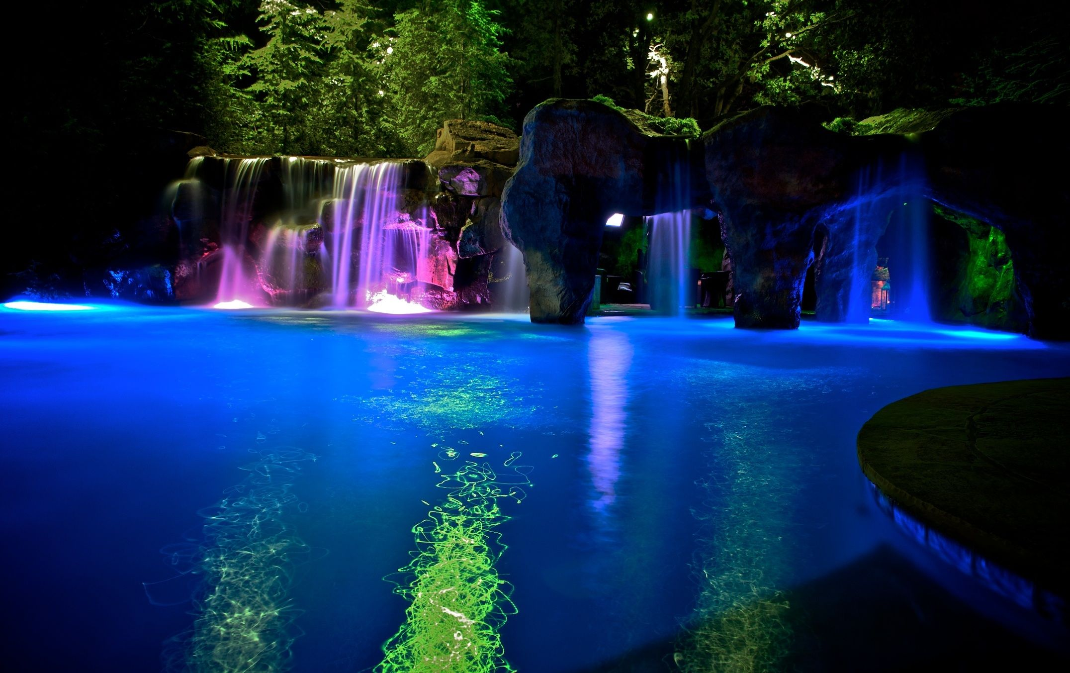 Luxury Swimming Pools With Waterfalls pool with multi-colored lighting that alternates during the
