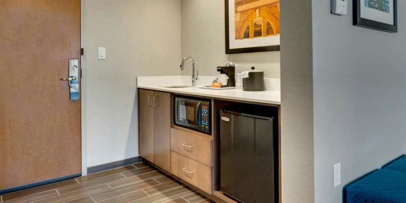 Hampton Inn And Suites Kitchenette Products Plain Style Wood Cabinet With Open Shelf For Microwave And Mini Fridge Wood Cabinets Hotel Style Quartz Countertops