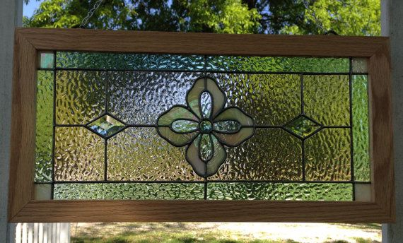 This beautiful stained glass art panel measures 11x 22. It is a new piece that I designed and made in my shop. It is signed and dated. The center flower has a green jewel. The inner petals of the flower are a clear iridescent glass. The outer petals are a cream iridescent glass. Which I also used for the four corners. There are two diamond bevels alongside of the flower. I used champagne pink (which is really peach in color) and Cornwall green muffle glass around the flower. The lead lines…