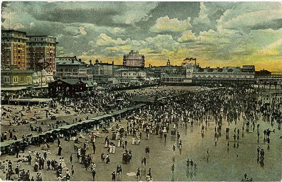 Vintage New Jersey postcard of people walking on the Atlantic City Boardwalk and beach in August.