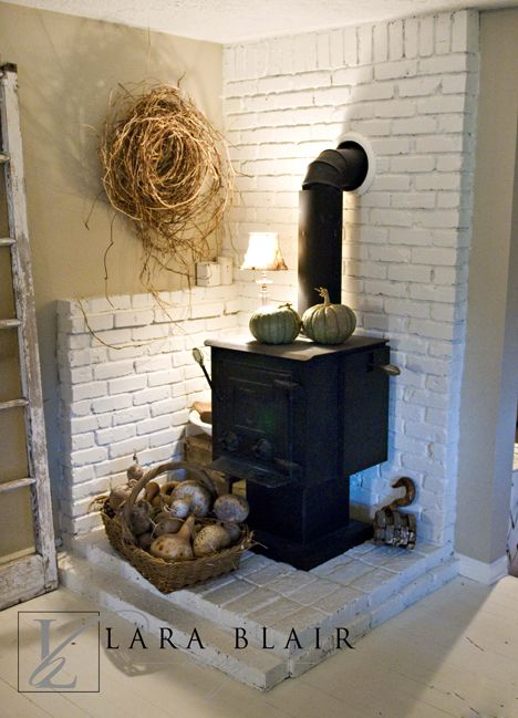 Not a fan of the white brick, but love the corner woodstove! I want a house  with a wood stove SOOOOO bad - Not Sure About The Assymetrical Wall Height But Good Idea For