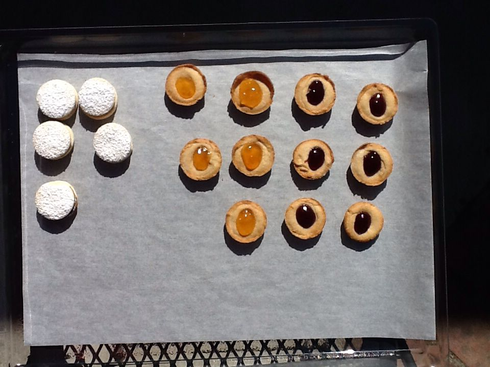 Thumb print cookies and tea cookies with caramel in the middle with powder sugar on the top
