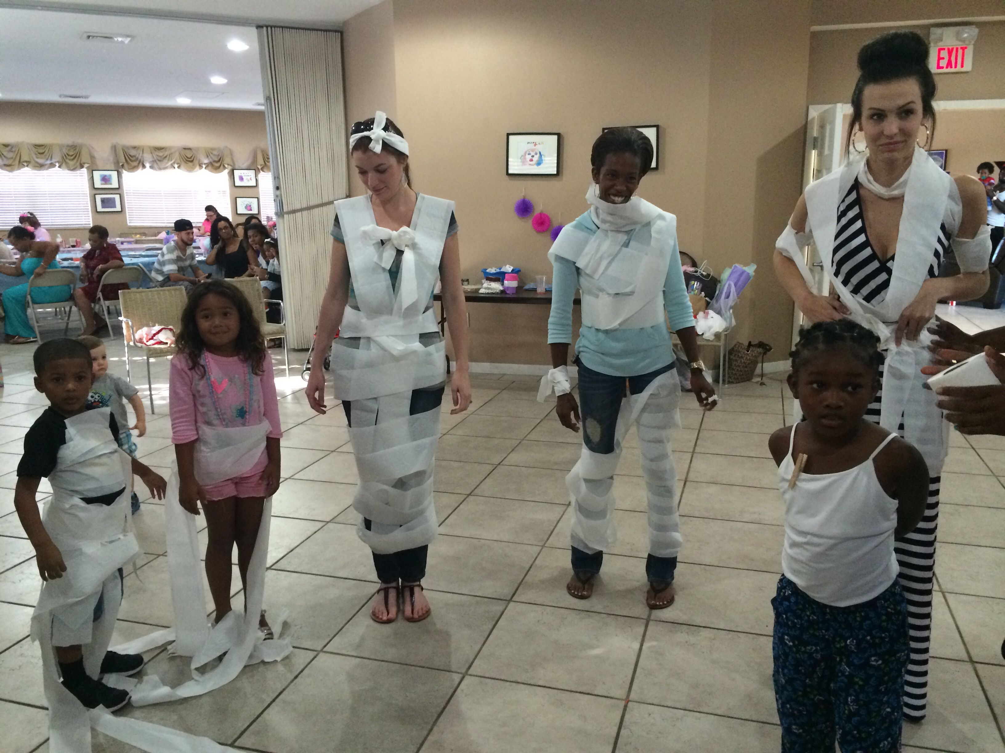 """Baby shower games Groups of 3 dress up """"big"""" baby with toilet paper"""