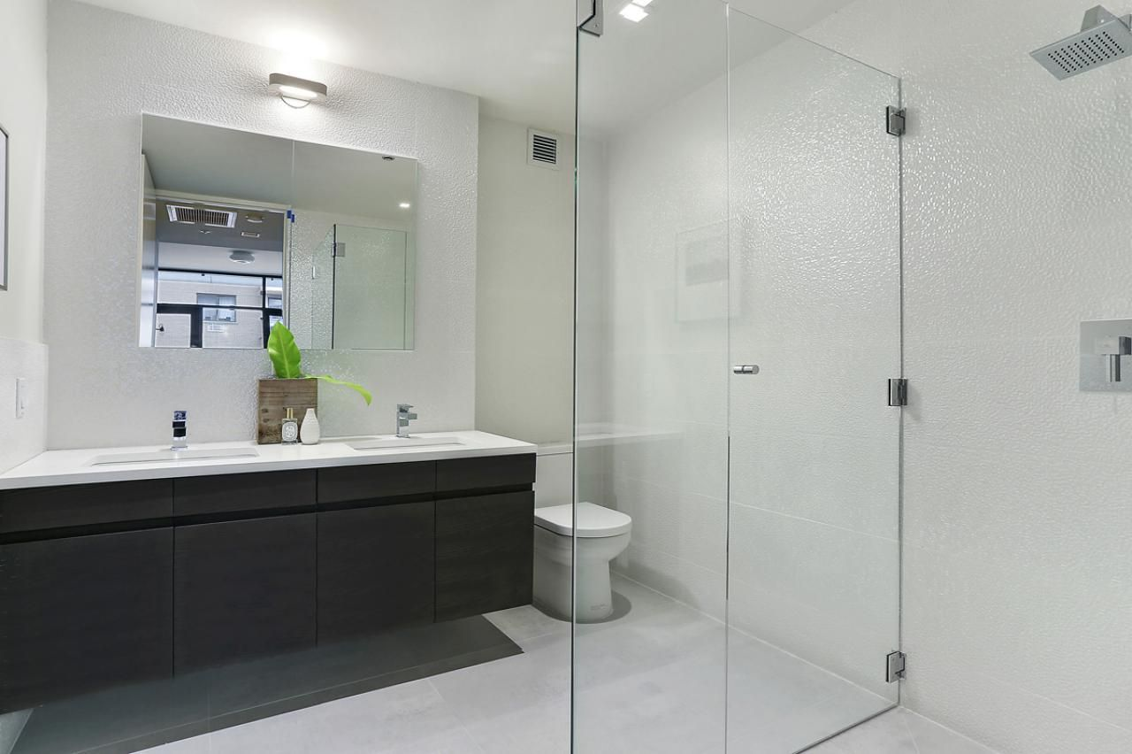 This modern white bathroom features an Italian cabinet design ...