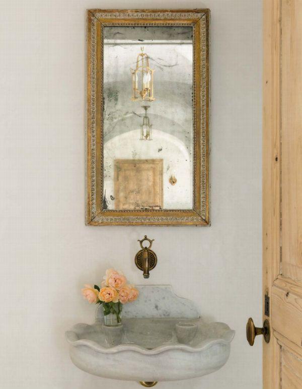 Powder room in a modern farmhouse with rustic decor, stone sink, and vintage mirror. #patinafarm #modernfarmhouse #bathroom