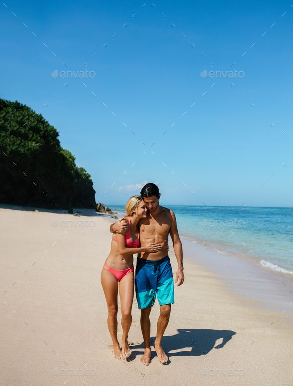 Romantic young couple on the beach by jacoblund. Shot of young man and woman walking on the tropical beach. Romantic couple strolling on the beach, enjoying summer va...