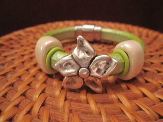 Pistachio licorice leather bracelet with antiqued silver flower focal bead, off-white ceramic slides and lime green o rings on Etsy, $30.00