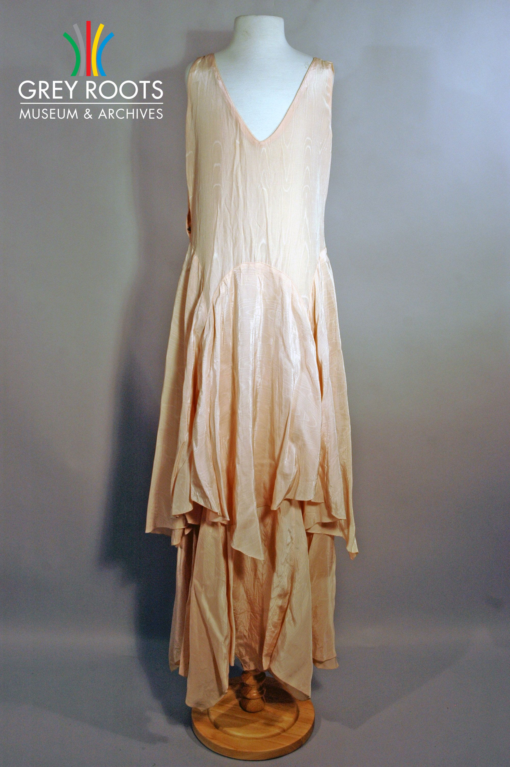 A long, pink, moire evening dress which features a double skirt and a v-neck. Grey Roots Museum & Archives Collection.