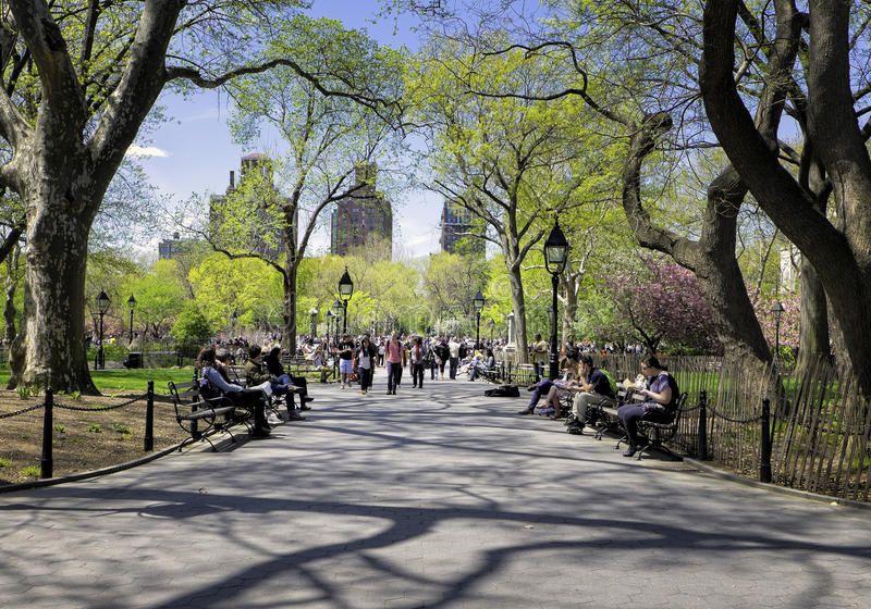 Washington Square Park New York People sit on benches and walk through Washing
