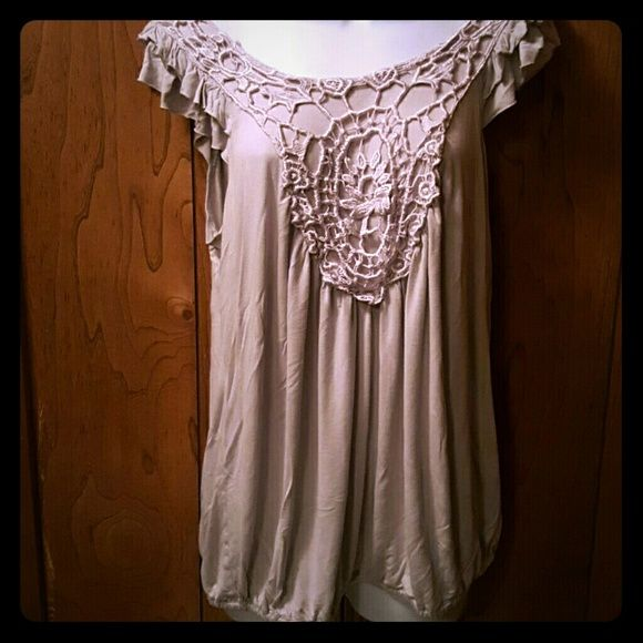 Summer Top This Grey flowy top is sure to turn heads. It's cute design on front and cute ruffles on the arms and the bottom of the shirt is loose fitting with a little stretch. Catch My I  Tops Camisoles