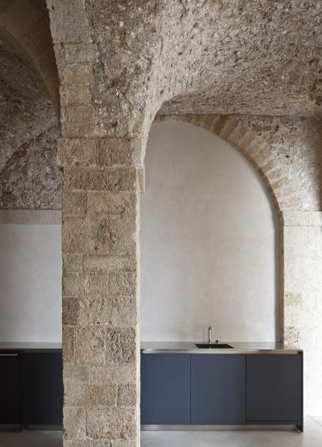 Wall coverings have been peeled away to reveal a vaulted stone ceiling that's several hundred years old inside this refurbished apartment in Tel Aviv.