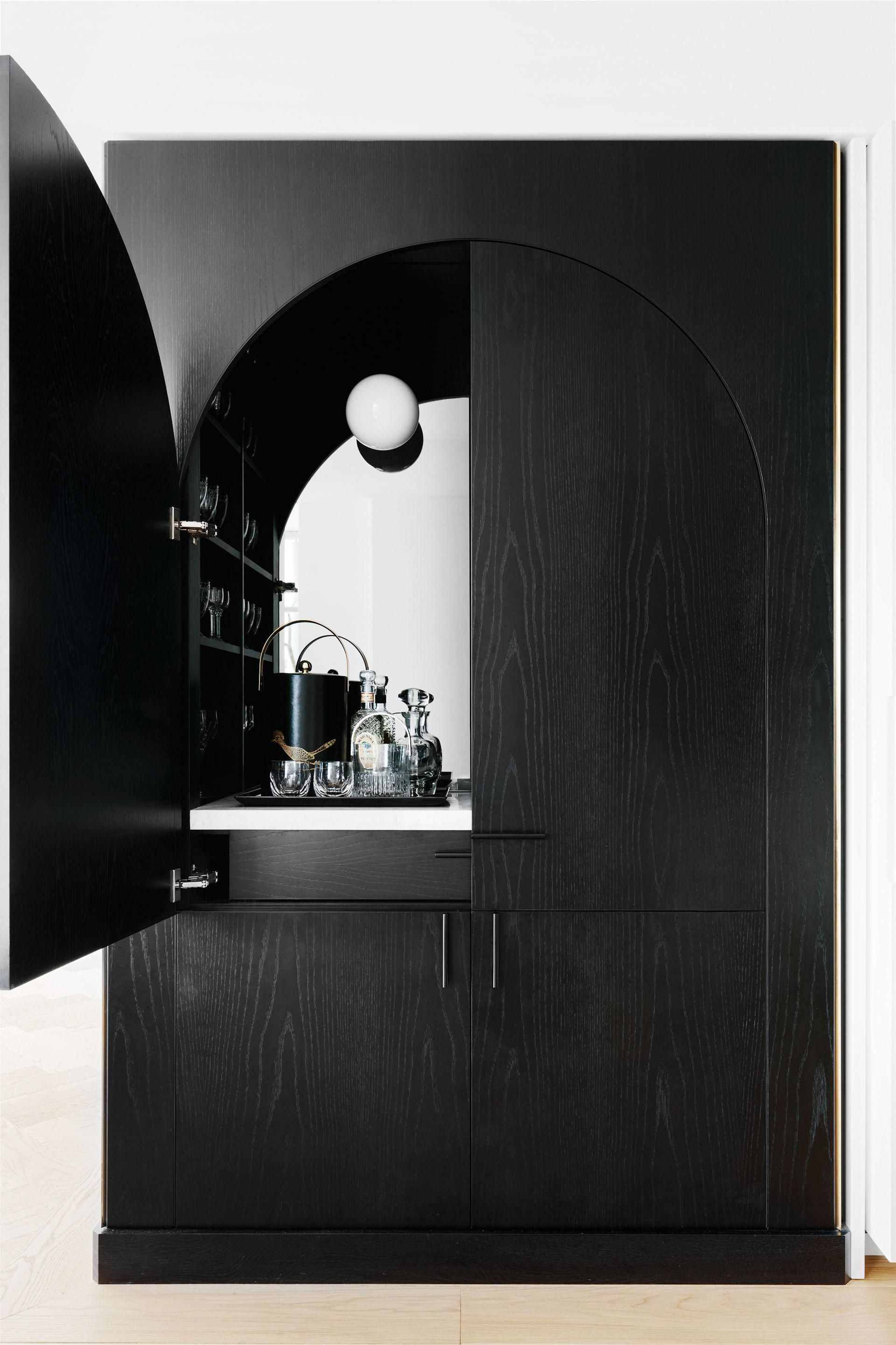 Suave and sophisticated, this sleek black hidden bar is accessible from both the living and dining areas of this Sydney Harbour apartment. Photography: Felix Forest | Styling: Steve Cordony | Story: Belle #luxuryhomes