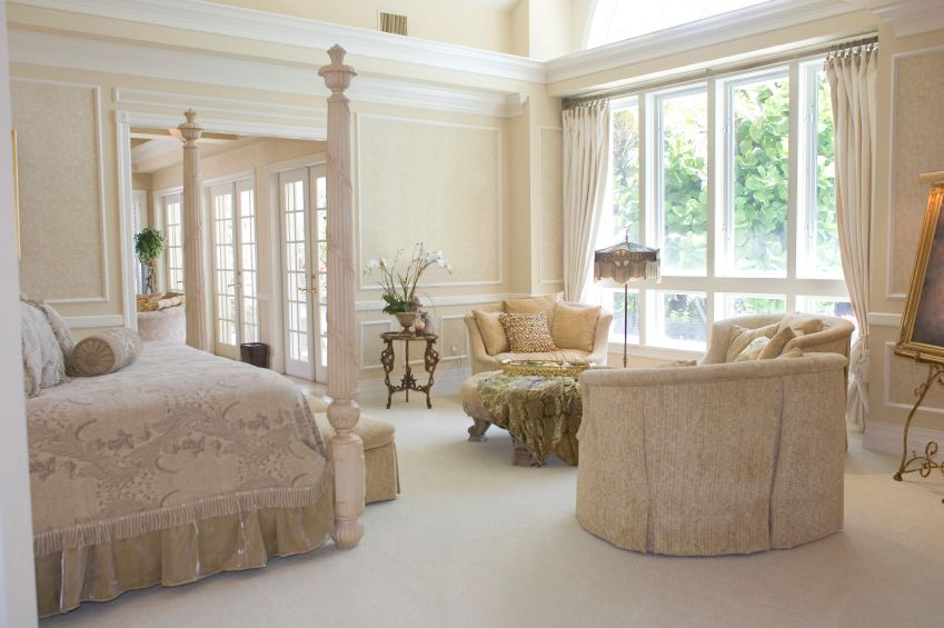 This White And Cream Bedroom Is Incredibly Traditional, With Soft White  Armchairs And A Painting In A Gilded Frame On A Floor Display.