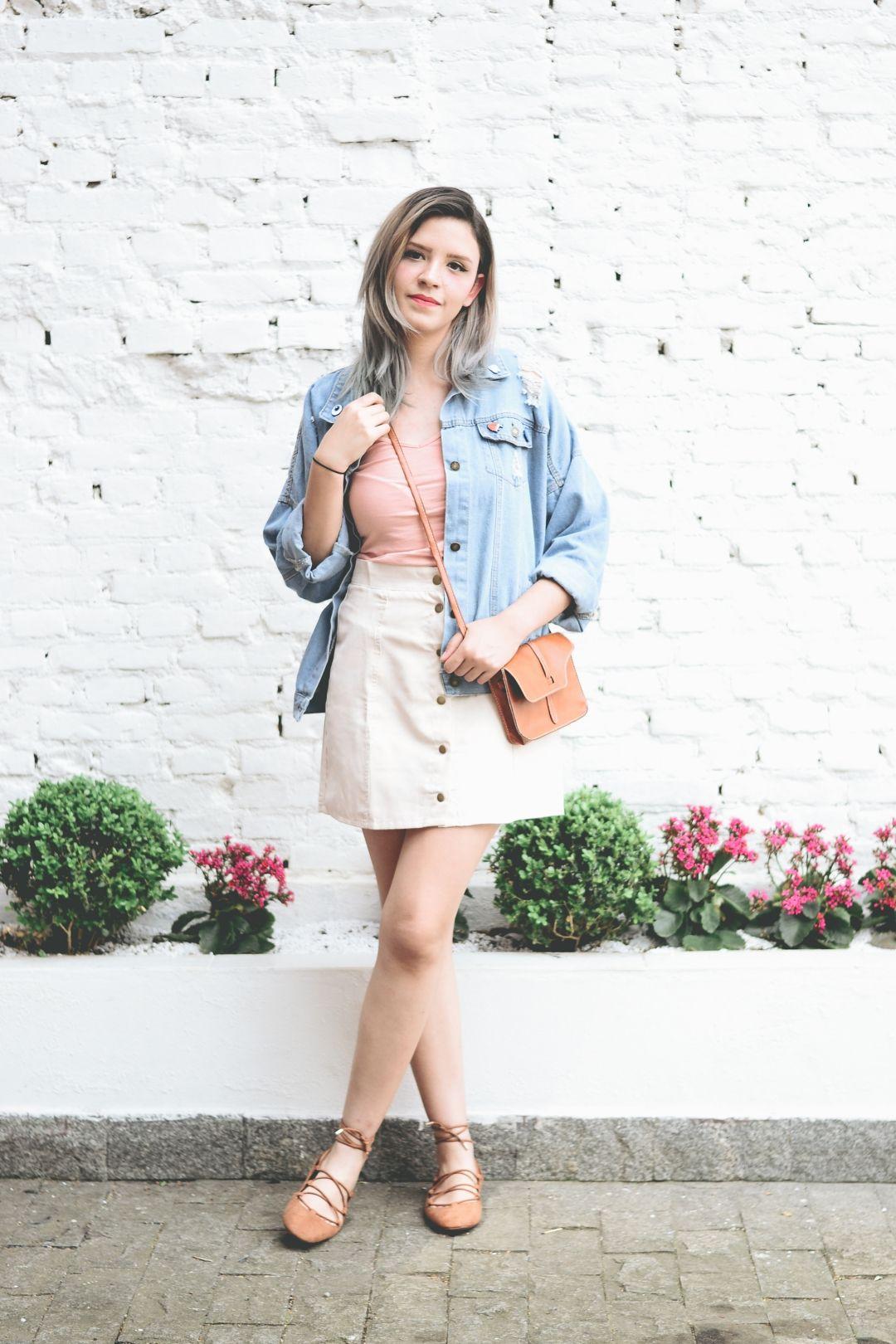 dd4e23791cbf3 Look de primavera com saia bege com botões na frente, sapatilha de amarrar  caramelo, blusa rose, jaqueta jeans oversized e bolsa caramelo.