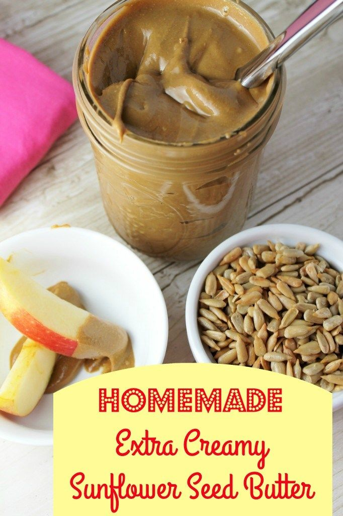 Optimized for pinterest vertical mage of fresh homemade creamy sunflower seed butter in a mason jar with a white bowl of whole sunflower seeds and a sliced apples with a red skin