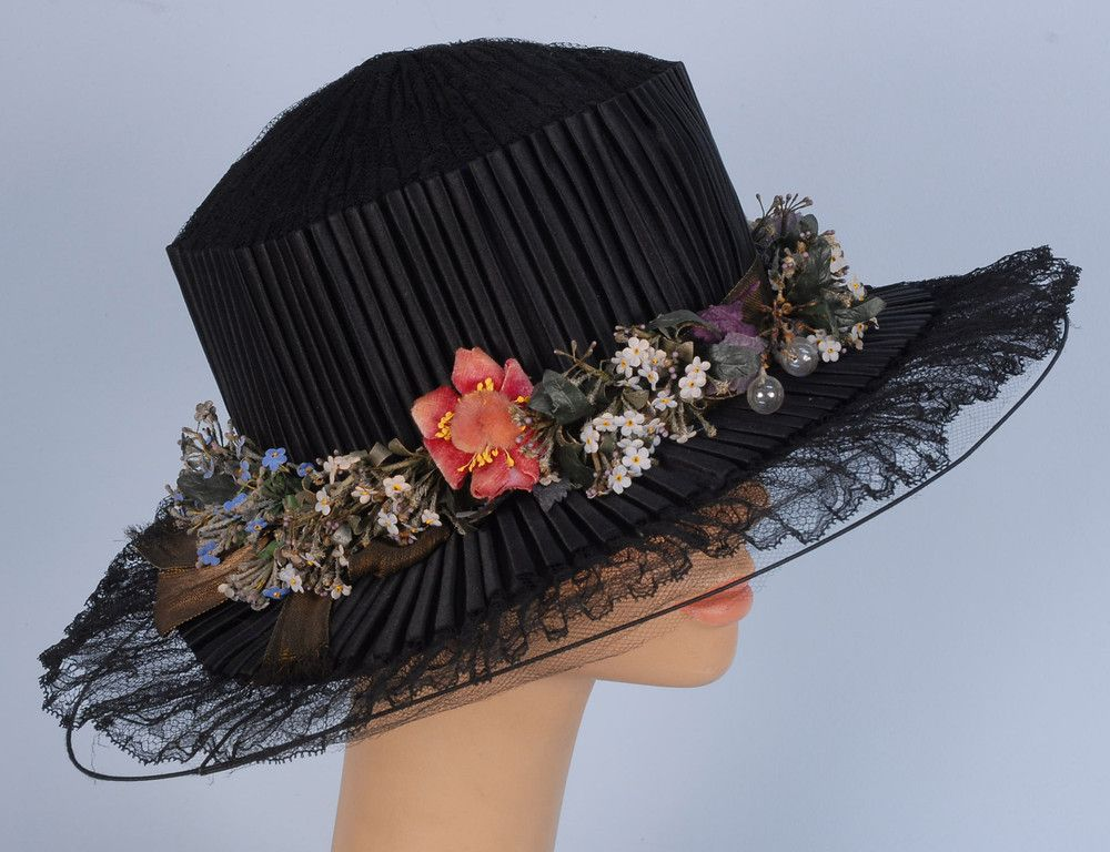 "Silk And Lace Wide Brim Hat - Flat Crown Of Black Lace,  Pleated Satin Sides Overlapping Sheer Black Lace Oval Brim Decorated With Gold Lame Ribbon, Cloth Flowers And Glass Bubbles, Under-Brim In Gold Lame - Label ""Gimbel Brothers New York, Philadelphia, Paris""     c.1900-1910"
