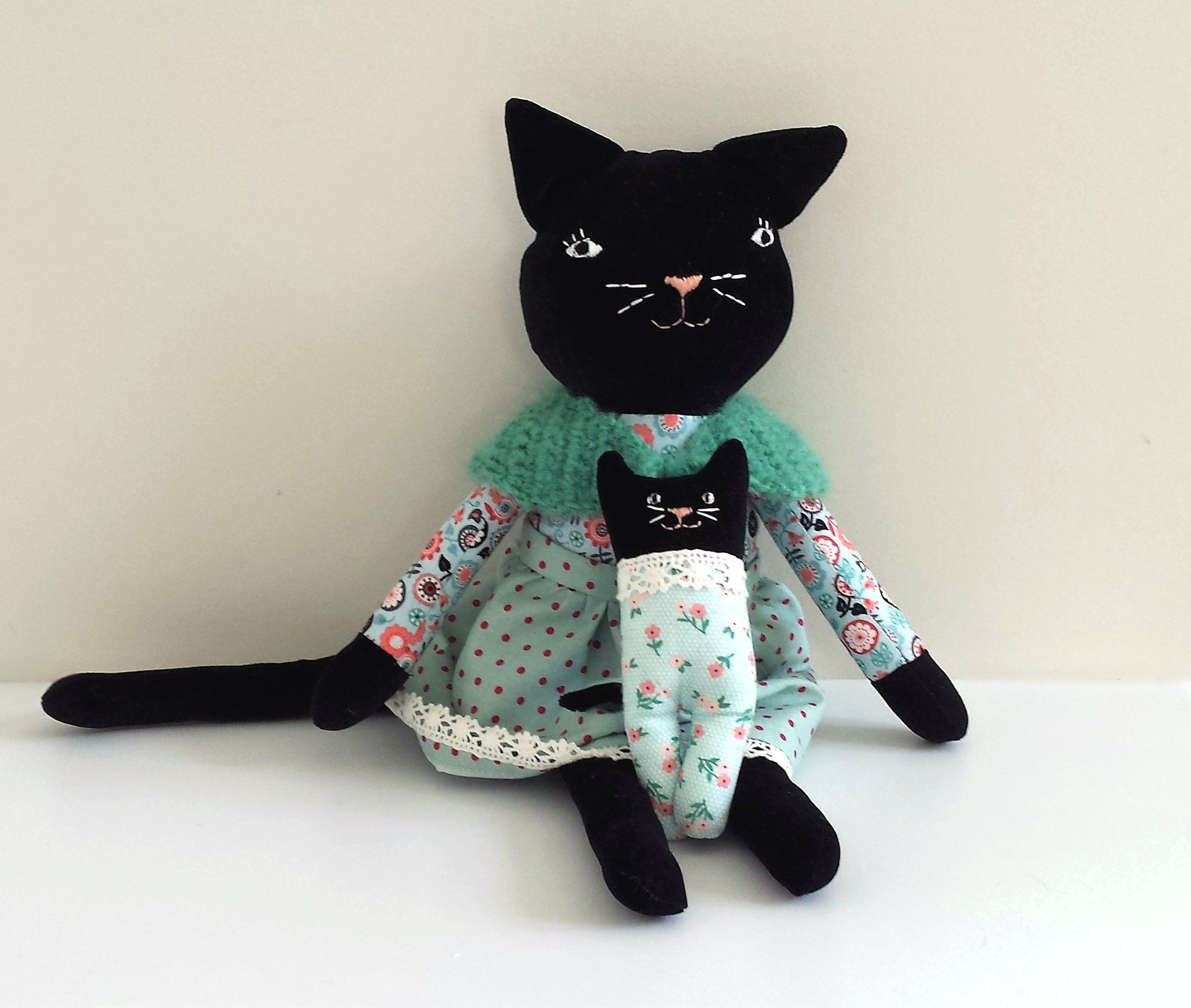 This one of a kind, handmade cat doll is named Moira.She has a black kitten that likes to hide in her quilted Christmas stocking. She measures approximately 43 cm (17 inches) tall from tip of her ears to her toes. Her kitten measures approximately 15 cm (6 inc) tall.Moira wears a removable skirt and a hand made crochet wrap with pompoms on the end of the ties.The kitten has a soft faux fur tail. This doll is suitable for a child over the age of 4 years old and require ...