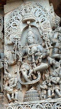 A picture of a sculpture of a eight-armed god dancing.
