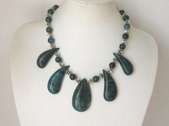 Sumptuous green and blue hues can be seen in this unusual chrysocolla tribal style gemstone necklace. The chunky gemstones have been inter-spaced with lantern style spacer beads with an antiqued silver tone finish. A statement stone necklace, the perfect accessory to compliment any outfit.  Dimensions: Necklace measures 18 (46 cm) Closes with a nickel free silver plated copper heart toggle clasp. Large pendant in the middle drapes 50 mm graduating to 40 mm at the last drop. Round gemstones…