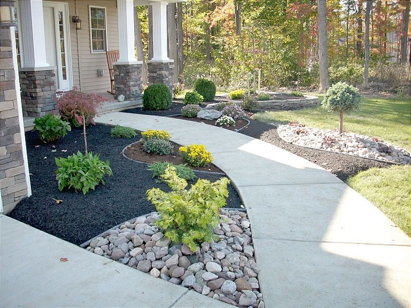 The Contrast Of Black Mulch And Stone Front Yard Landscaping