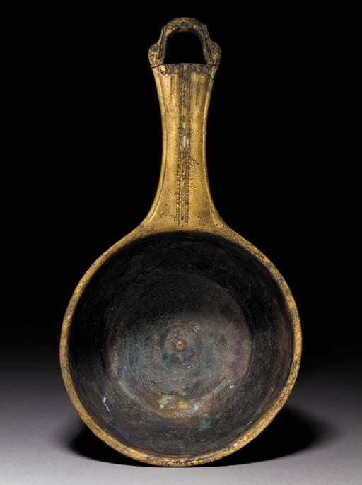 A ROMAN BRONZE CASSEROLE Circa 1st Century B.C. The deep bowl with a rounded rim and lathe-turned concentric circles in the tondo, along the shoulder, and on the underside, the flat handle with a stamped medial line of ornament including tongues at the end, terminating in a loop formed from two stylized duck heads, with two workshop inscriptions stamped near the terminal 13½ in. (34.3 cm) long