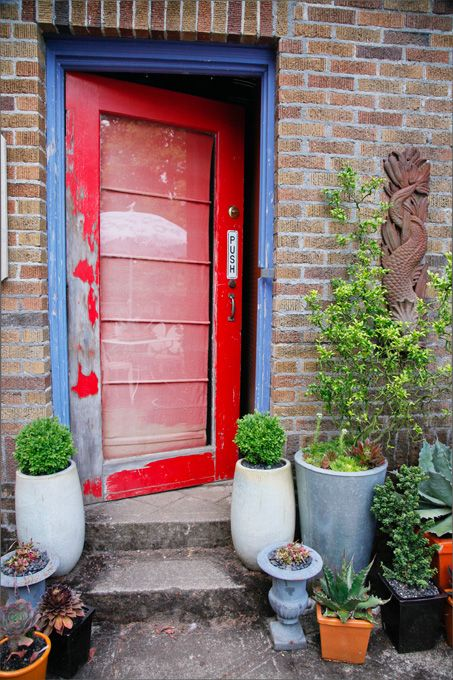 A rustic red door trimmed in blue adds a focal point to the back of the house.