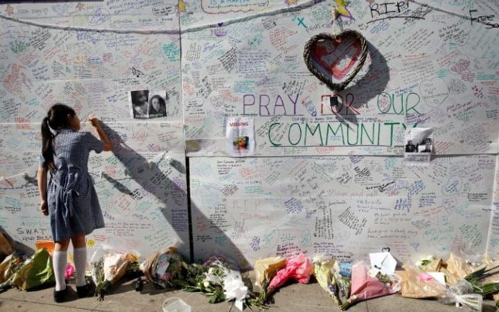 A school girl writes a message on a wall for the victims and in support for those affected by the massive fire in Grenfell Tower, in London.A massive fire raced through the 24-story high-rise apartment building in west London early Wednesday.
