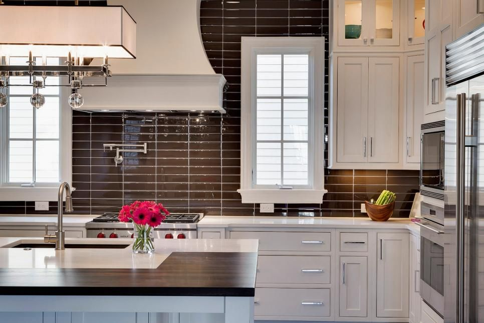 White shaker cabinets pair with brown glass tile walls in this transitional kitchen  beautiful also au