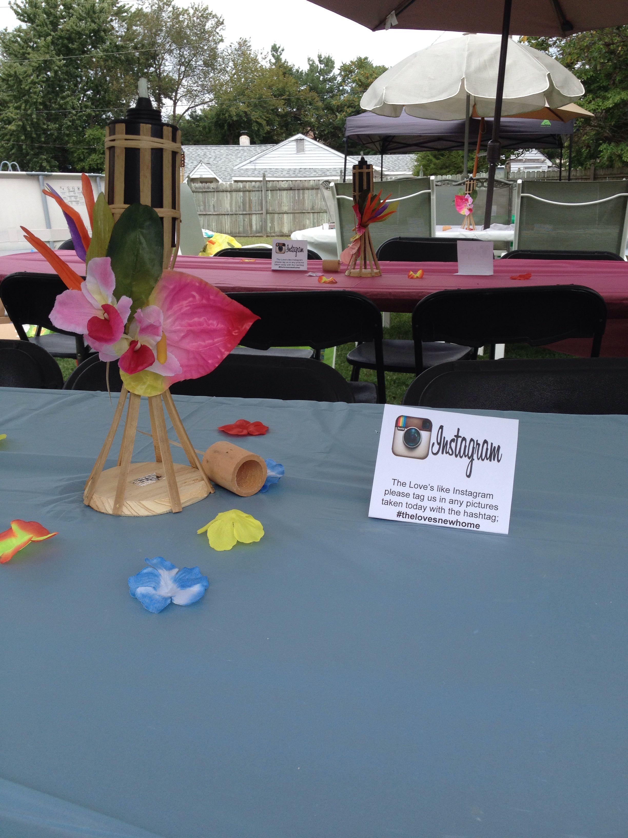 Tiki Torches Decorated With Hawaiian Flowers Used As Centerpieces