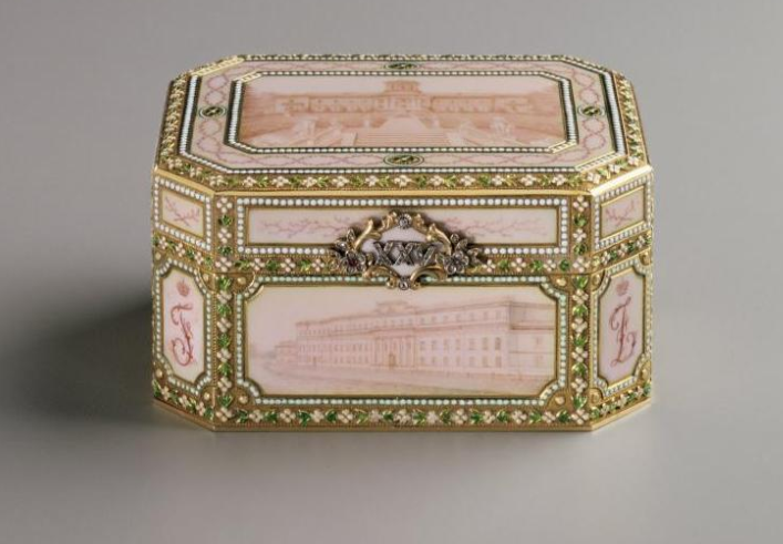 In 1907 Felix and Nikolai Iusupov gave this Fabergé music box to their parents, Prince Felix and Princess Zenaida, as a twenty-fifth wedding anniversary present. The Roman numerals XXV, set in diamonds, form the thumbpiece, and the initials of the four family members appear in the lower corner panels of the octagonally shaped Louis XVI-style box. Six of the Iusupov palaces are depicted in sepia enamel panels on the music box's top, bottom, and four sides. When opened, the music box plays…
