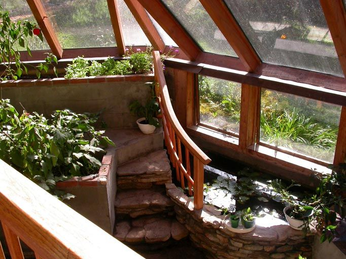 Terraced greenhouse or sun room planters with fish pond for Koi pond greenhouse