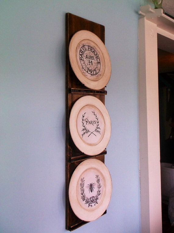 This rustic plate rack holds three plates. It is distressed, and has ...