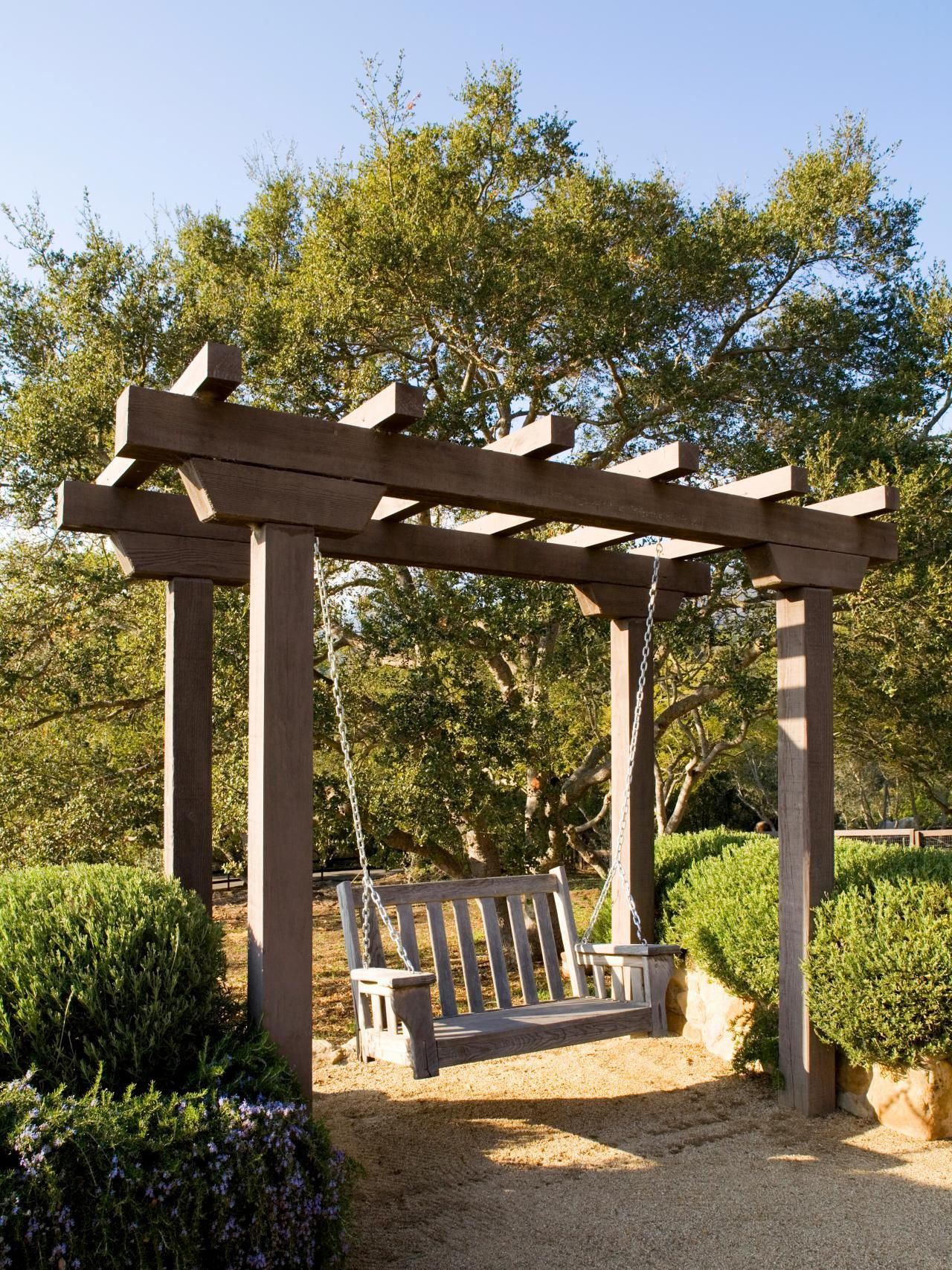 a lovely wooden arbor with attached swing is bordered by