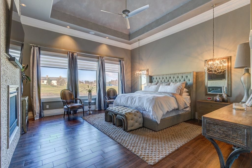 Transitional master bedroom with high ceiling hardwood floors pendant light crown molding Interior designers edmond ok