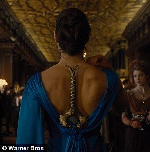 Warning Gal Wears A Blue Ball Gown With Her Sword Tucked In The Back At A Wonder Woman Blue Dress Wonder Woman Gal Gadot