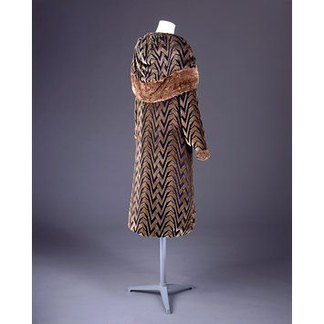 This low-slung, black and gold satin and velvet evening coat has a deep, shawl collar, which can be used as a hood, and long sleeves. French 1925