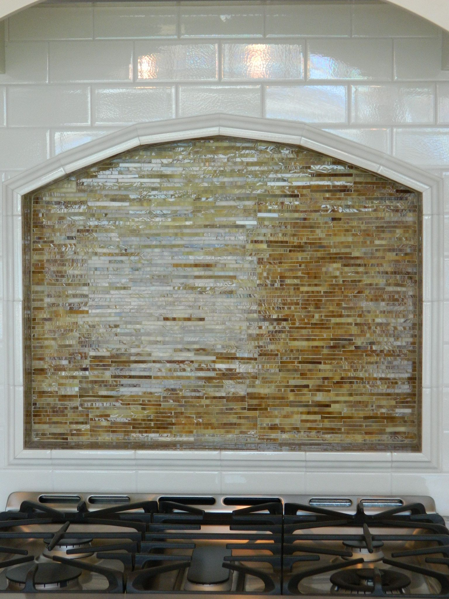 Framed arched kitchen niche behind cooktop with stacked glass tile avb custom home builders commercial construction company white subway tile backsplashkitchen dailygadgetfo Choice Image
