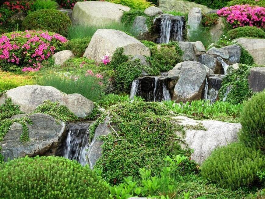 Ein Wasserspiel neben wild Moos und Reben gibt eine Steingarten ein