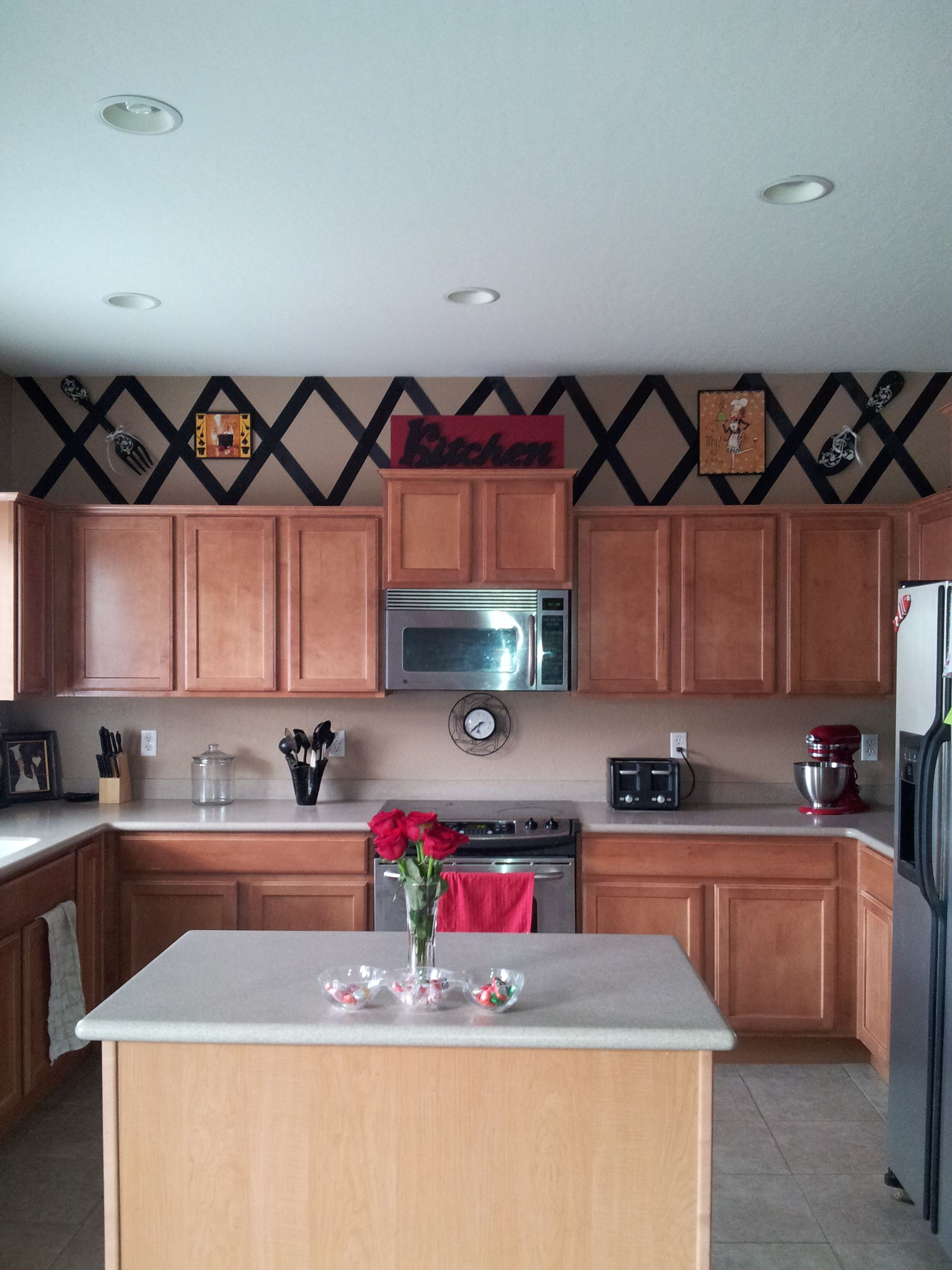 My kitchen :) I took black ribbon and hot glued it to the wall. added a few pics and called it good! All of this for under $100.