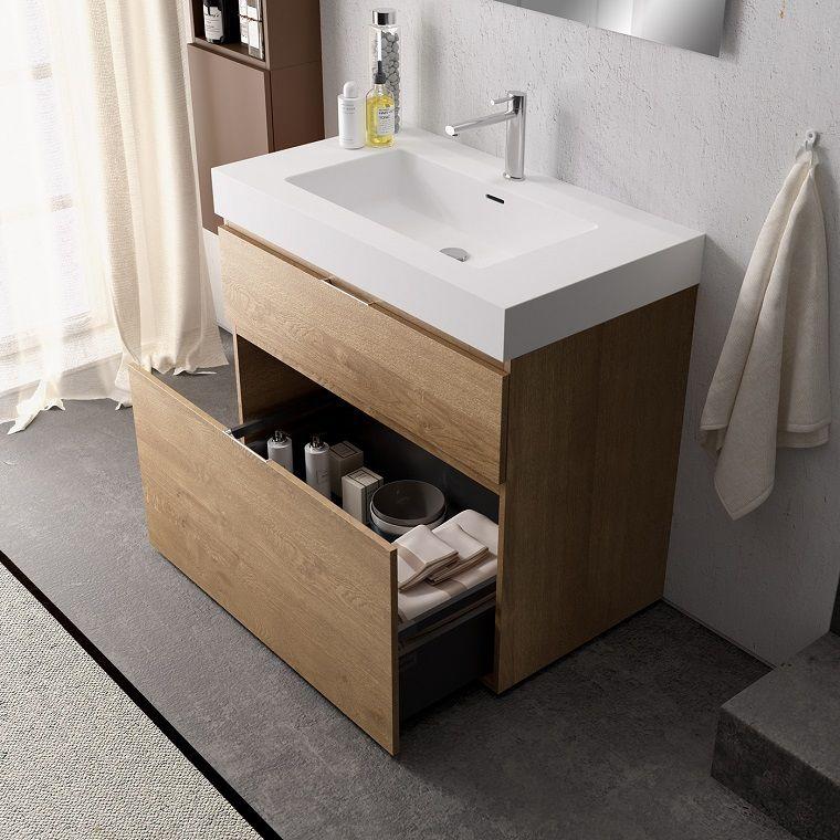 Mobile di legno con lavabo in appoggio e cassetti con maniglie di ...