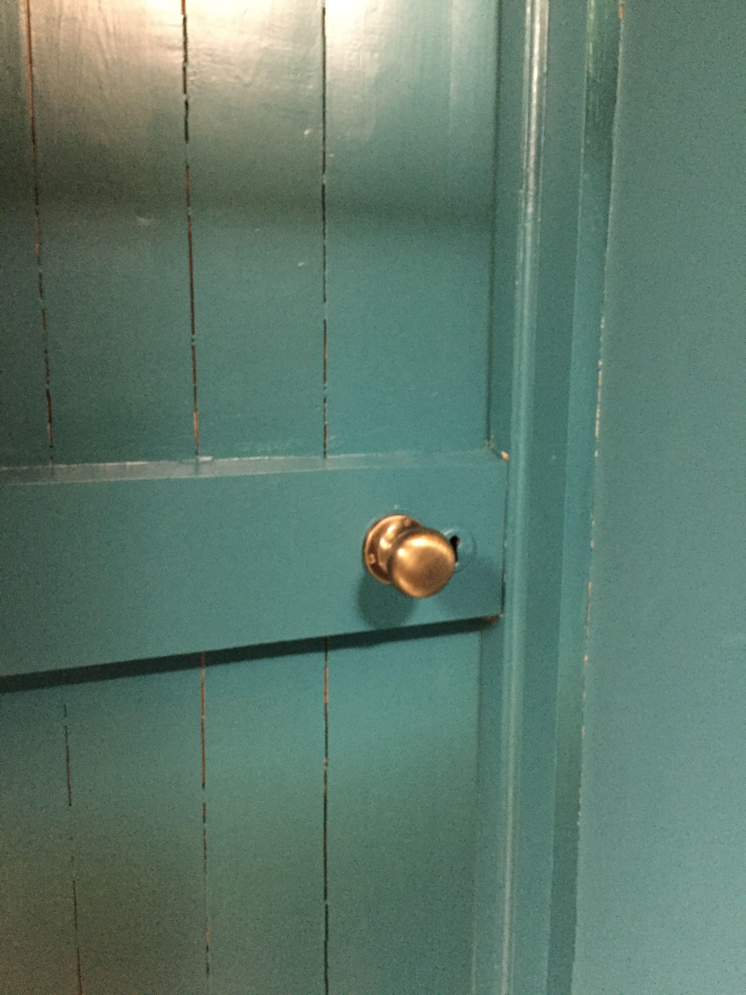 Antique brass door knob on plank door (painted in Farrow & Ball ...