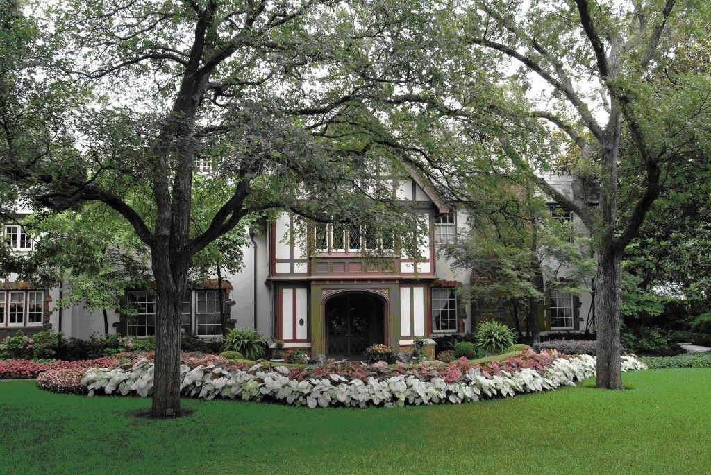 The Front Yard Of This Dallas Tudor Style House Has A Large Tree Bright Green Gr Lawn And Row Pink Caladiums White Framing