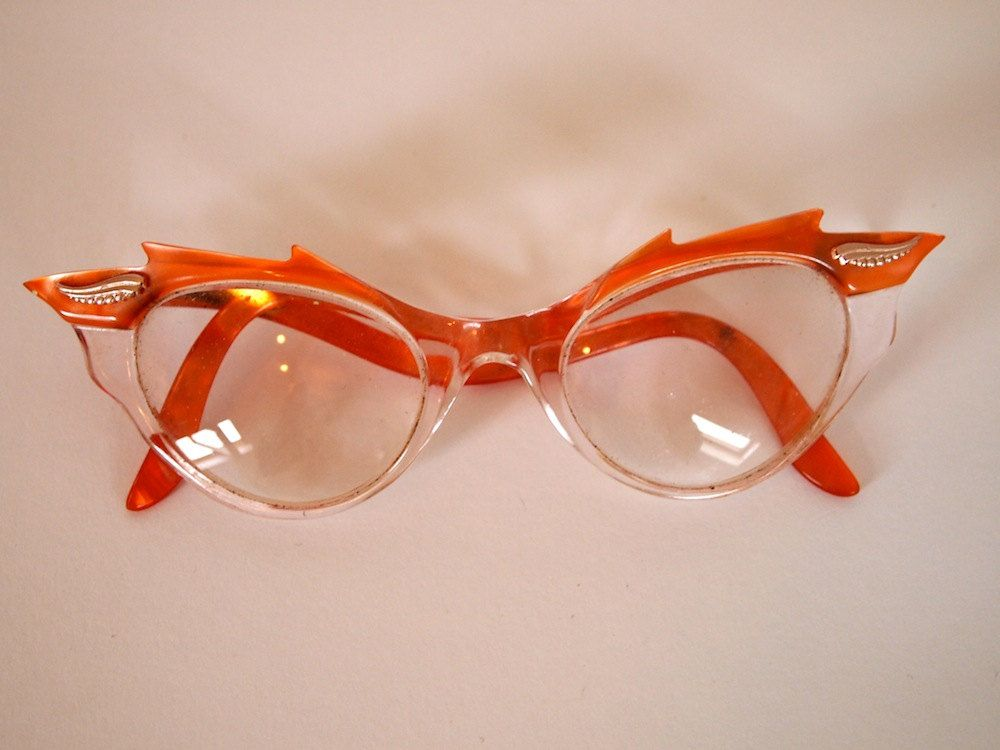 33f565aa4bb Vintage 1950s decorative flame style detail pearlescent orange and clear  cat eye glasses with pink metallic detail.