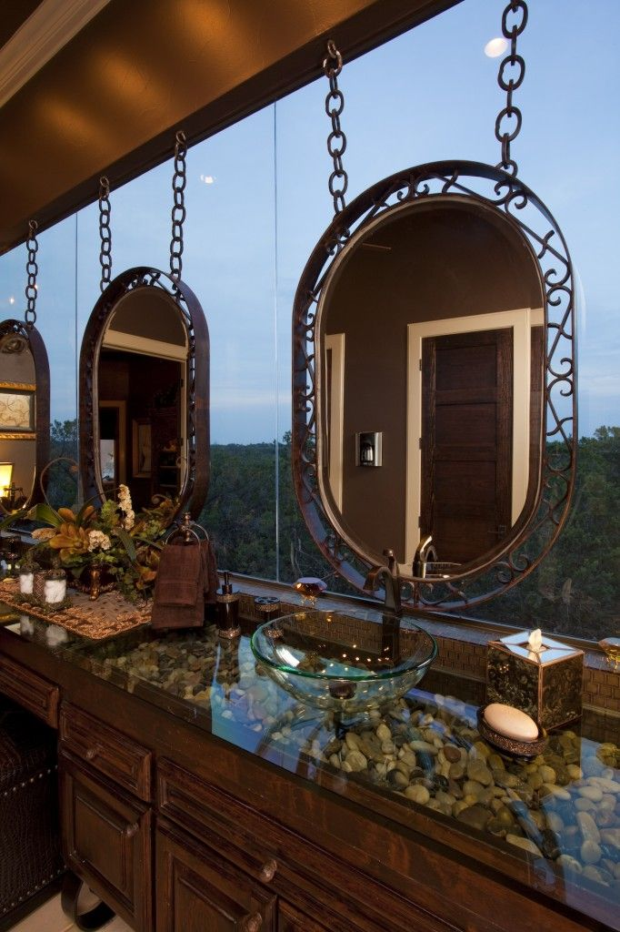Now that's what I call a bathroom with a view!  Interesting river rock under a glass countertop with vessel sinks.  Would be great is a mountain home.