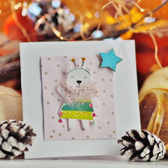 Photo of Weihnachtskarte Netter Bär mit pastellrosa handgestricktem Schal auf pastellrosa silbernem Tupfenhintergrund verziert mit türkisfarbenem Stern