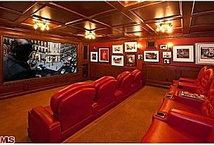 dream media room with wood ceilings and artwork with red leather!
