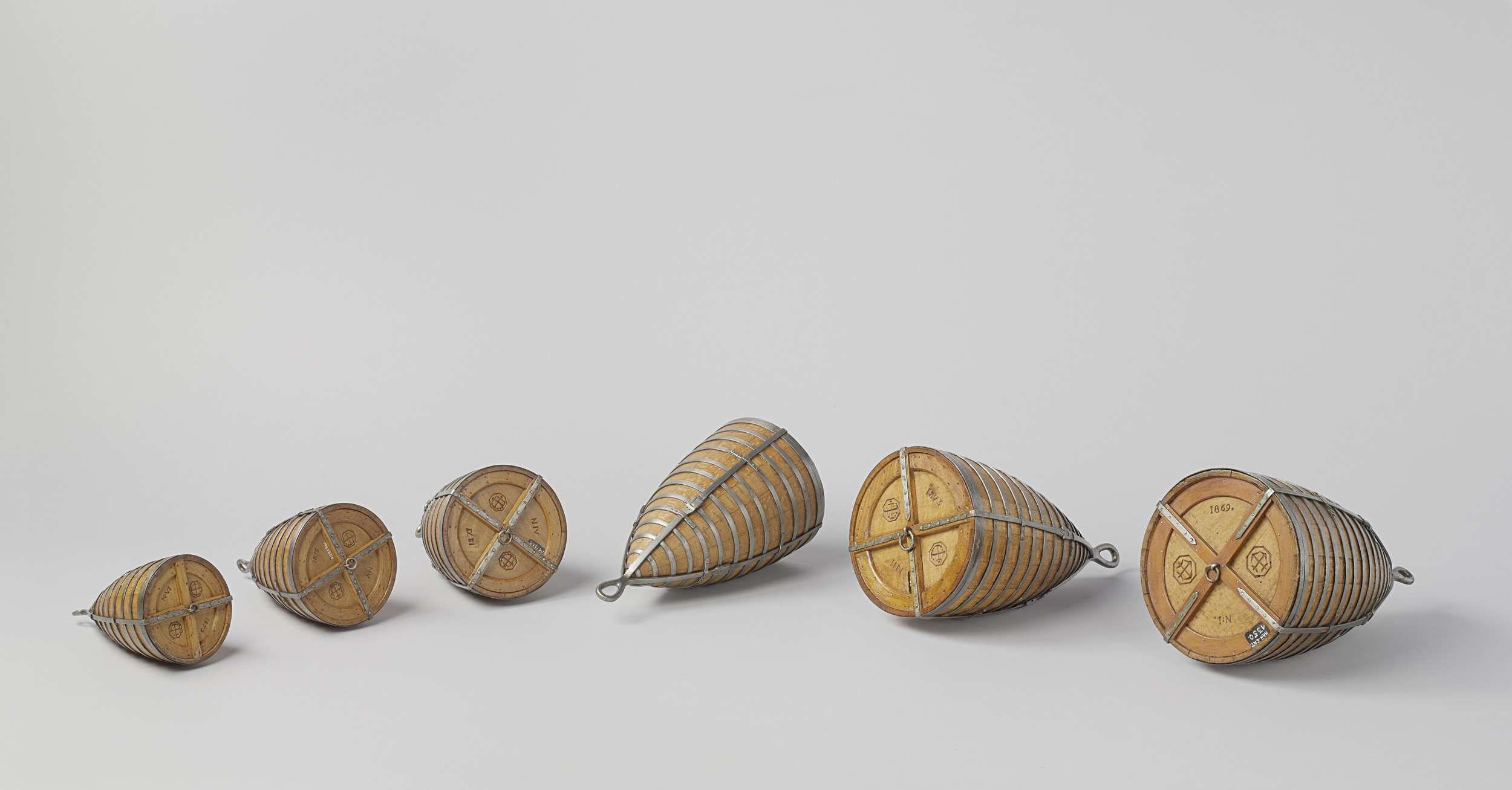 Rijkswerf Enkhuizen | Zes modellen van boeien, Rijkswerf Enkhuizen, 1869 - 1873 | Zes modellen van boeien (buiktonnen) van verschillende formaten. Zij hebben conische lichamen met een scherp uiteinde en een ronde platte bovenkant met een ring in het midden. Zoals vaten zijn zij samengesteld van duigen en hoepels. Onderaan zit een oog voor de ankerketting. Alle modellen zijn met gekruiste ankers gemerkt. Schaal 1:10 (archief).
