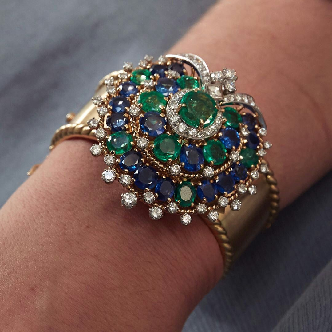 This spectacular bangle comprising emeralds sapphires and diamonds